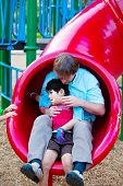 Caucasian Father Helping Disabled Son Down Slide At Playground