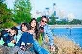 image of babysitter  - Disabled boy in wheelchair with family outdoors on sunny day with city skyline in background - JPG