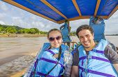 Couple of tourists traveling in touristic boat down the Beni river in Bolivian jungle (Rurrenabaque region)