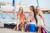 Three beautiful young women with shopping bags near the sea.