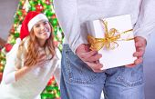 Pretty cheerful woman excited to see her husband hide gift behind back, with pleasure receiving festive present, happy Christmas holiday concept
