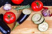 Set of vegetables on cutting board, eggplant, garlic, tomatoes, rosemary, chili pepper