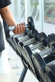 Strong Women Hand Takes A Heavy Dumbbell In Gym