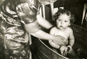 GERMANY, CIRCA 1938 -  Vintage photo of mother washing her baby girl in a bathtub