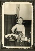 GERMANY, CIRCA 1938 -  Vintage photo of baby girl washing his teddy bear in a wash basin