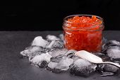 Glass Jar With Salmon Caviar Standing In The Middle Of Ice Cubes On Black Slate Plate