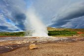 Iceland in the summer. Gushing geyser Strokkur. High column of hot water and steam from the crater of the geyser.