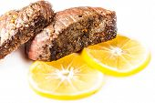 Sliced Roasted Meat With Slices Of Lemon Closeup