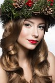 Beautiful girl with a wreath of fir branches and cones. New Year image.