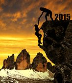 Silhouette girls climbs into the New Year 2015. In the background Tre Cime di Lavaredo.