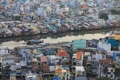 Poor houses in Ho Chi Minh Riverside cityscape view with Ben Nghe or Tau Hu canal in sunset