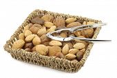 assorted nuts in a wicker basket with a nutcracker on a white background