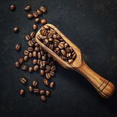 Coffee beans and an old wooden scoop on dark background