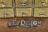 web design - text in vintage letterpress metal type blocks on a grunge wood with rustic drawer cabinet in background
