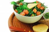 green salad with salmon and tomatoes in green bowl