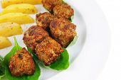 served meatballs on basil leaf with gold potatoes