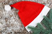Santa red hat with snowflakes and branch of fir-tree on wooden background