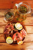 sweet fruits with tea pot on wood