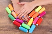 Multicolor female manicure with colorful thread on wooden background