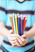 Bunch of colored pencils in children's hands