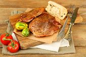 Roasted meat and vegetables on cutting board, on wooden table background