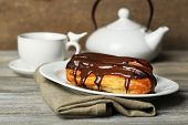 Tasty eclairs and cup of tea on wooden table