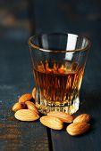 Dessert liqueur Amaretto with almond nuts, on dark wooden table