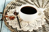 Cup of coffee with lace doily, spoon and coffee beans on wicker stand, on color wooden background