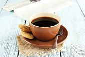 Cup of coffee with newspaper on burlap cloth, on color wooden background