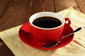 Cup of coffee on saucer with spoon on color napkin on wooden table background