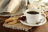 Cup of coffee with cookies, star anise and cinnamon on burlap cloth on wooden table background