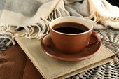 Cup of coffee on book near plaid on wooden table background