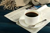 Cup of coffee with saucer and spoon on newspaper on color wooden background