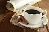 Cup of coffee with saucer, spoon and cinnamon on burlap cloth near newspaper on wooden table background