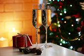 Two glass with champagne with chocolates and present box on table on Christmas tree and fireplace background