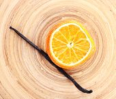 Dried orange with vanilla beans on wooden background