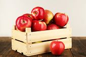Crate of apples on wooden table, on white background