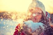 stock photo of blowing  - Beauty Winter Girl Blowing Snow in frosty winter Park - JPG