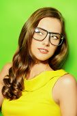 Beauty portrait of a positive young woman in spectacles and bright yellow dress over green background. Beauty, fashion. Optics.