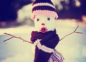 small snowman in snow with a knitted hat and scarf on toned with a retro vintage instagram filter effect
