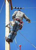 foto of lineman  - an electrical lineman working on a line - JPG