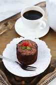 Yummy chocolate cupcake and cup of coffee on tray