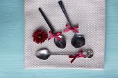 Metal spoons and dark red flower on napkin on light blue wooden background