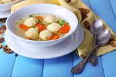 Soup with meatballs and noodles in bowls on color wooden background