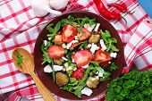 Eggplant salad with tomatoes, arugula and feta cheese, on napkin, on color wooden background