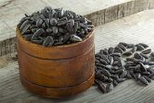 stock photo of sunflower-seeds  - Roasted and salted sunflowers seeds in their shells in bowl over old wood background - JPG
