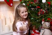 Little girl near Christmas tree on fireplace with candles background