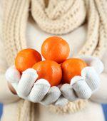 Fresh ripe mandarins in female hands, close-up