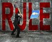 Businessman Holding Hammer Hitting Red Rule Word On Concrete Wall