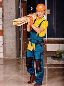 picture of millwright  - Man in builder uniform carry boards indoor - JPG